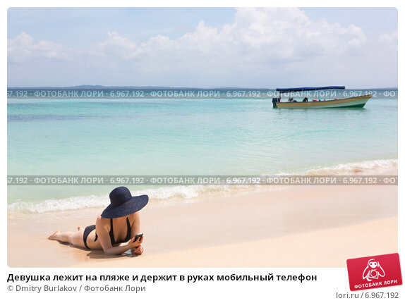 Девушка лежит на пляже и держит в руках мобильный телефон. Стоковое фото, фотограф Dmitry Burlakov / Фотобанк Лори
