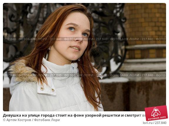Девушка на улице города стоит на фоне узорной решетки и смотрит вверх, фото № 237840, снято 28 марта 2008 г. (c) Артем Костров / Фотобанк Лори