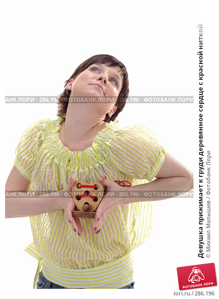 Девушка прижимает к груди деревянное сердце с красной ниткой, фото № 286196, снято 12 мая 2008 г. (c) Михаил Малышев / Фотобанк Лори