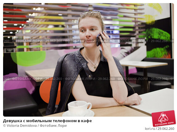 Девушка с мобильным телефоном в кафе. Стоковое фото, фотограф Victoria Demidova / Фотобанк Лори