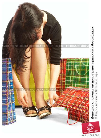 Девушка с покупками поправляет пряжки на босоножках, фото № 83080, снято 14 мая 2007 г. (c) Андрей Армягов / Фотобанк Лори