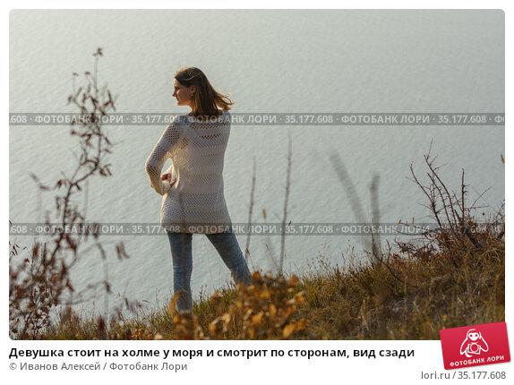 Девушка стоит на холме у моря и смотрит по сторонам, вид сзади. Стоковое фото, фотограф Иванов Алексей / Фотобанк Лори