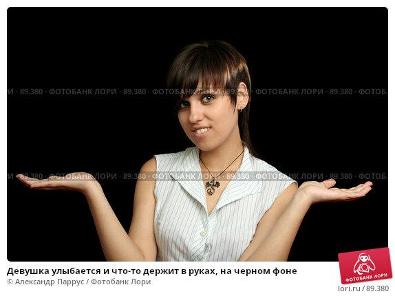 Девушка улыбается и что-то держит в руках, на черном фоне, фото № 89380, снято 31 мая 2007 г. (c) Александр Паррус / Фотобанк Лори