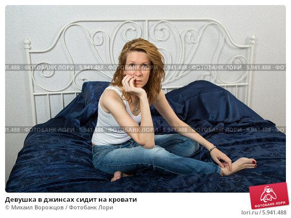 Купить «Девушка в джинсах сидит на кровати», фото № 5941488, снято 12 июня 2013 г. (c) Михаил Ворожцов / Фотобанк Лори