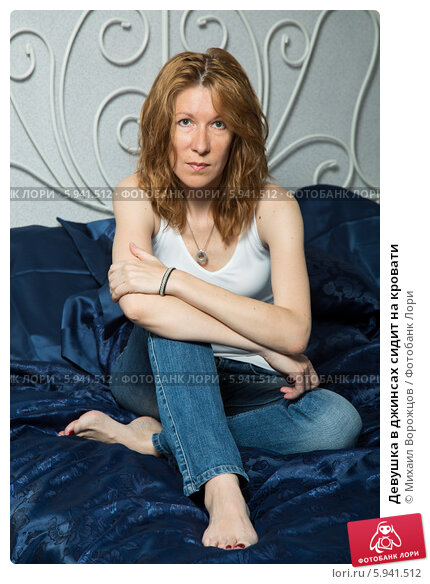 Купить «Девушка в джинсах сидит на кровати», фото № 5941512, снято 12 июня 2013 г. (c) Михаил Ворожцов / Фотобанк Лори