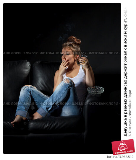 Блондинка курит на диване