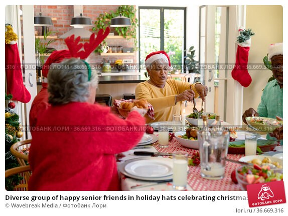 Diverse group of happy senior friends in holiday hats celebrating christmas together at home. Стоковое фото, агентство Wavebreak Media / Фотобанк Лори