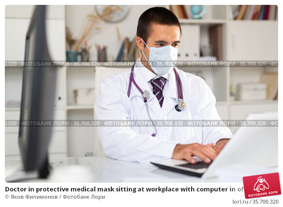 Doctor in protective medical mask sitting at workplace with computer in office. Стоковое фото, фотограф Яков Филимонов / Фотобанк Лори