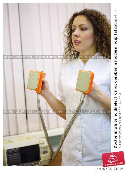 Купить «Doctor in white holds electroshock probes in modern hospital cabinet, noface», фото № 28171108, снято 20 ноября 2015 г. (c) Losevsky Pavel / Фотобанк Лори