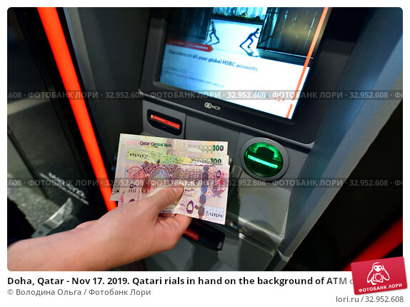 Doha, Qatar - Nov 17. 2019. Qatari rials in hand on the background of ATM of HSBC Bank. Редакционное фото, фотограф Володина Ольга / Фотобанк Лори