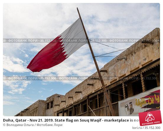 Doha, Qatar - Nov 21. 2019. State flag on Souq Waqif - marketplace is noted for selling traditional garments. Редакционное фото, фотограф Володина Ольга / Фотобанк Лори