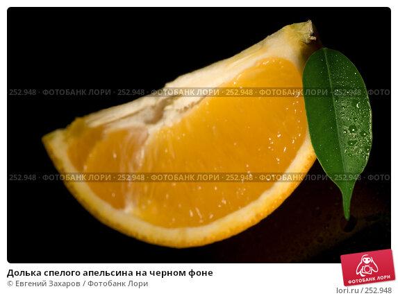 Долька спелого апельсина на черном фоне, эксклюзивное фото № 252948, снято 13 апреля 2008 г. (c) Евгений Захаров / Фотобанк Лори