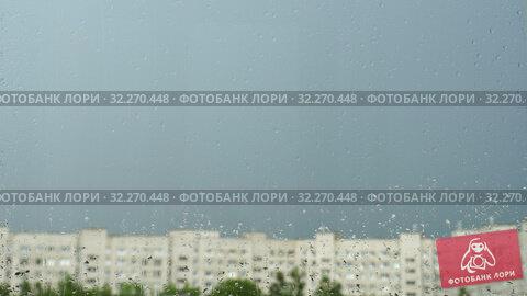 Купить «Drops of water on window glass. Summer rain in city, blue sky, blurry silhouettes of houses and green trees. 4K video», видеоролик № 32270448, снято 16 октября 2019 г. (c) Dmitry Domashenko / Фотобанк Лори