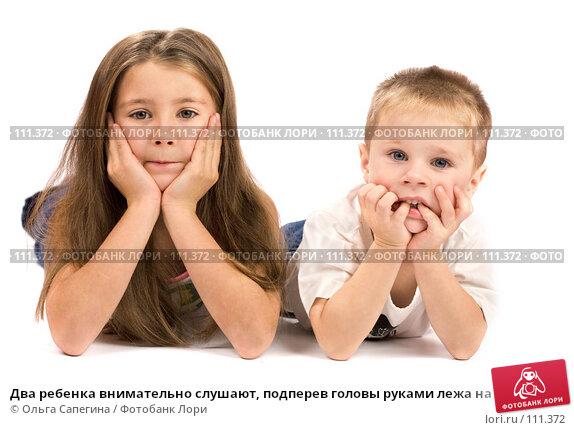 Два ребенка внимательно слушают, подперев головы руками лежа на полу, фото № 111372, снято 3 ноября 2007 г. (c) Ольга Сапегина / Фотобанк Лори