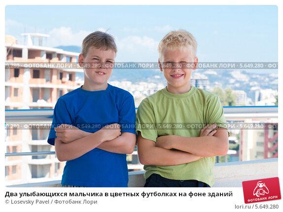 Купить «Два улыбающихся мальчика в цветных футболках на фоне зданий», фото № 5649280, снято 7 июля 2012 г. (c) Losevsky Pavel / Фотобанк Лори