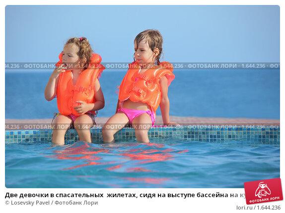 Купить «Две девочки в спасательных  жилетах, сидя на выступе бассейна на курорте», фото № 1644236, снято 9 июля 2009 г. (c) Losevsky Pavel / Фотобанк Лори