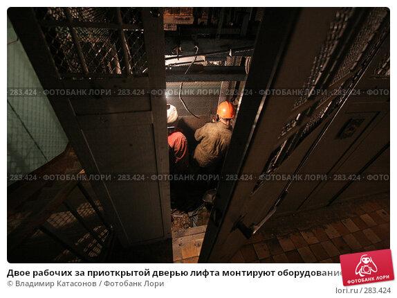Двое рабочих за приоткрытой дверью лифта монтируют оборудование, фото № 283424, снято 28 июля 2017 г. (c) Владимир Катасонов / Фотобанк Лори