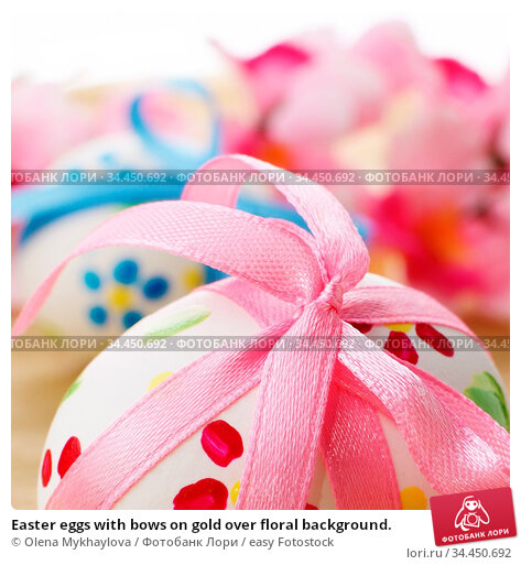 Easter eggs with bows on gold over floral background. Стоковое фото, фотограф Olena Mykhaylova / easy Fotostock / Фотобанк Лори