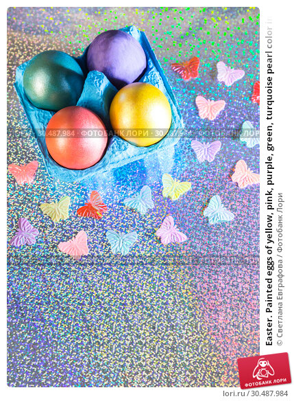 Купить «Easter. Painted eggs of yellow, pink, purple, green, turquoise pearl color in blue packaging on a holographic rainbow background with a copy space», фото № 30487984, снято 31 марта 2019 г. (c) Светлана Евграфова / Фотобанк Лори