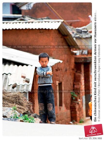 Ein chinesisches Kind mit verschraenkten Armen vor Haeusern eines... Стоковое фото, фотограф Zoonar.com/Rees Peter / easy Fotostock / Фотобанк Лори