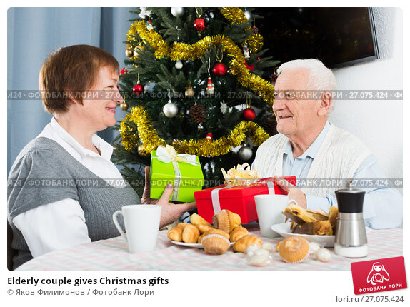 Elderly couple gives Christmas gifts, фото № 27075424, снято 20 октября 2017 г. (c) Яков Филимонов / Фотобанк Лори