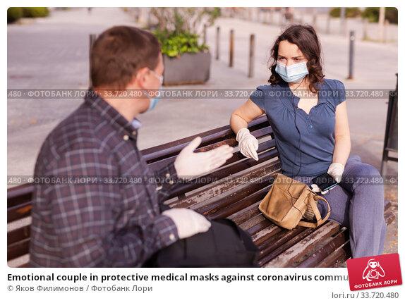 Купить «Emotional couple in protective medical masks against coronavirus communicate sittig on bench», фото № 33720480, снято 9 июля 2020 г. (c) Яков Филимонов / Фотобанк Лори