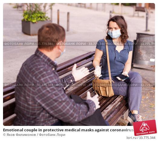 Купить «Emotional couple in protective medical masks against coronavirus communicate sittig on bench», фото № 33775344, снято 9 июля 2020 г. (c) Яков Филимонов / Фотобанк Лори