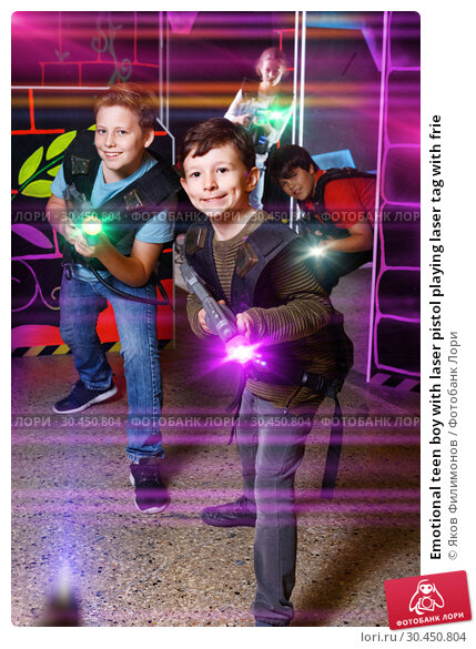 Emotional teen boy with laser pistol playing laser tag with frie. Стоковое фото, фотограф Яков Филимонов / Фотобанк Лори