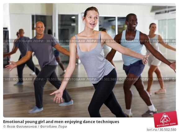 Купить «Emotional young girl and men enjoying dance techniques», фото № 30502580, снято 30 июля 2018 г. (c) Яков Филимонов / Фотобанк Лори