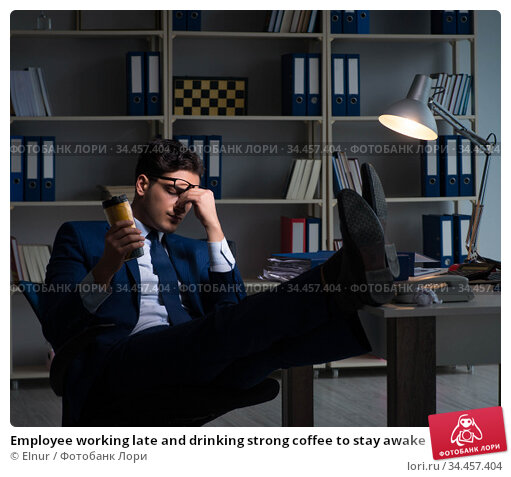 Employee working late and drinking strong coffee to stay awake. Стоковое фото, фотограф Elnur / Фотобанк Лори