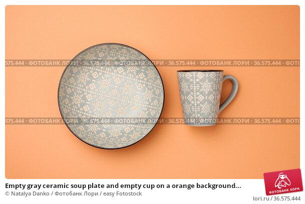 Empty gray ceramic soup plate and empty cup on a orange background... Стоковое фото, фотограф Natalya Danko / easy Fotostock / Фотобанк Лори