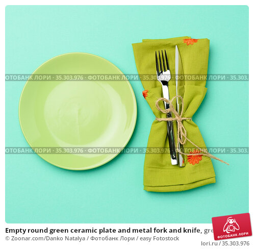 Empty round green ceramic plate and metal fork and knife, green background... Стоковое фото, фотограф Zoonar.com/Danko Natalya / easy Fotostock / Фотобанк Лори