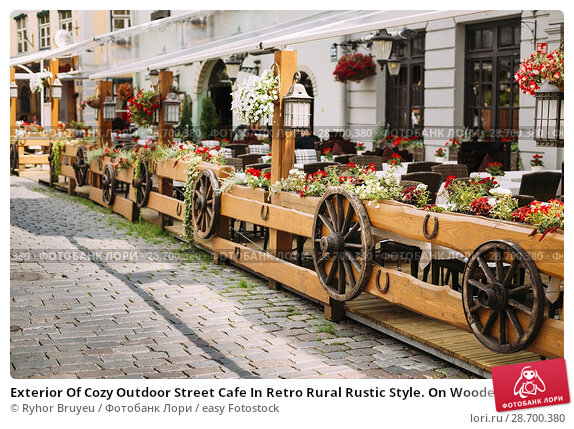 Купить «Exterior Of Cozy Outdoor Street Cafe In Retro Rural Rustic Style. On Wooden Wall Of Cafe Or Restaurant Hanging Wooden Wheels From Peasants Carts.», фото № 28700380, снято 2 июля 2016 г. (c) easy Fotostock / Фотобанк Лори