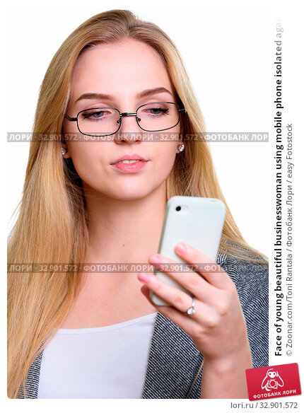 Face of young beautiful businesswoman using mobile phone isolated against white background. Стоковое фото, фотограф Zoonar.com/Toni Rantala / easy Fotostock / Фотобанк Лори