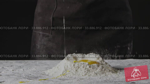 Купить «Falling egg into pile of flour on a black background. Process of preparing dough for homemade pasta. Slow motion, Full HD video, 240fps, 1080p.», видеоролик № 33886912, снято 4 июля 2020 г. (c) Ярослав Данильченко / Фотобанк Лори