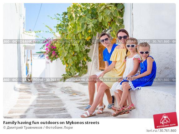Купить «Family having fun outdoors on Mykonos streets», фото № 30761860, снято 21 августа 2016 г. (c) Дмитрий Травников / Фотобанк Лори