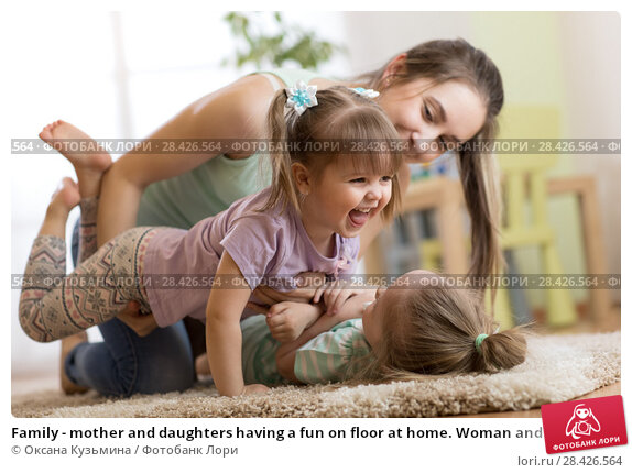 Купить «Family - mother and daughters having a fun on floor at home. Woman and children relaxing together.», фото № 28426564, снято 25 мая 2018 г. (c) Оксана Кузьмина / Фотобанк Лори