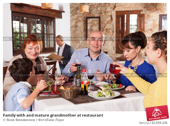 Family with and mature grandmother at restaurant. Стоковое фото, фотограф Яков Филимонов / Фотобанк Лори