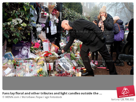 Купить «Fans lay floral and other tributes and light candles outside the home of singer George Michael in memory of the popular performer. His Range Rover has...», фото № 28700332, снято 28 декабря 2016 г. (c) age Fotostock / Фотобанк Лори