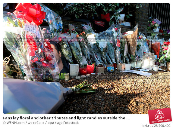Купить «Fans lay floral and other tributes and light candles outside the home of singer George Michael in memory of the popular performer. His Range Rover has...», фото № 28700400, снято 28 декабря 2016 г. (c) age Fotostock / Фотобанк Лори