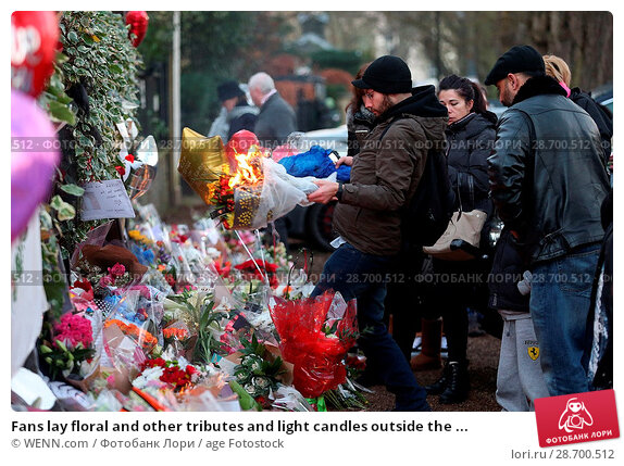 Купить «Fans lay floral and other tributes and light candles outside the home of singer George Michael in memory of the popular performer. His Range Rover has...», фото № 28700512, снято 28 декабря 2016 г. (c) age Fotostock / Фотобанк Лори