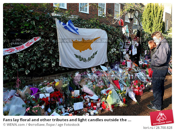 Купить «Fans lay floral and other tributes and light candles outside the home of singer George Michael in memory of the popular performer. His Range Rover has...», фото № 28700828, снято 28 декабря 2016 г. (c) age Fotostock / Фотобанк Лори