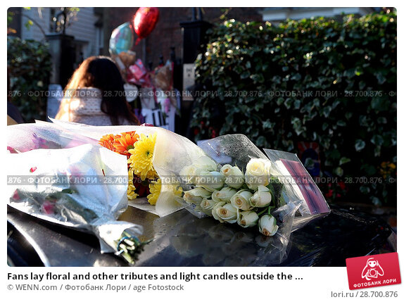Купить «Fans lay floral and other tributes and light candles outside the home of singer George Michael in memory of the popular performer. His Range Rover has...», фото № 28700876, снято 28 декабря 2016 г. (c) age Fotostock / Фотобанк Лори