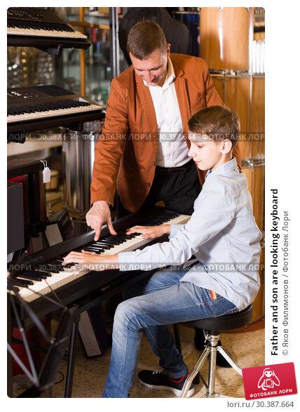 Купить «Father and son are looking keyboard», фото № 30387664, снято 29 марта 2017 г. (c) Яков Филимонов / Фотобанк Лори