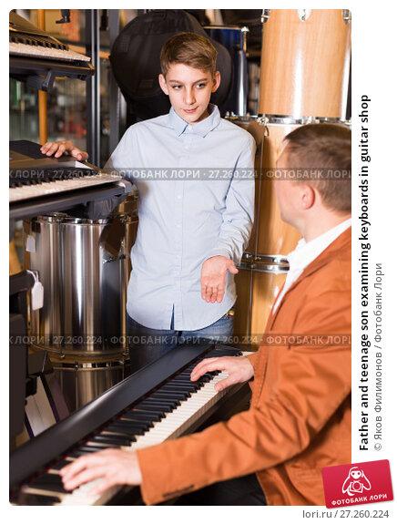 Купить «Father and teenage son examining keyboards in guitar shop», фото № 27260224, снято 29 марта 2017 г. (c) Яков Филимонов / Фотобанк Лори