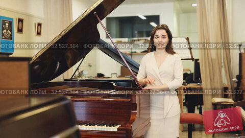 Купить «Female assistant or customer at piano music store», видеоролик № 32527364, снято 12 мая 2019 г. (c) Яков Филимонов / Фотобанк Лори