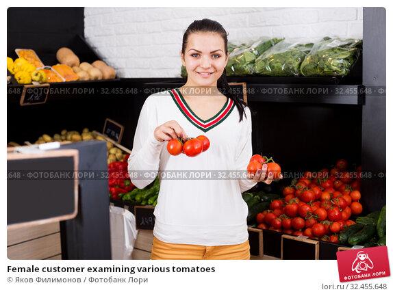 Купить «Female customer examining various tomatoes», фото № 32455648, снято 23 ноября 2016 г. (c) Яков Филимонов / Фотобанк Лори