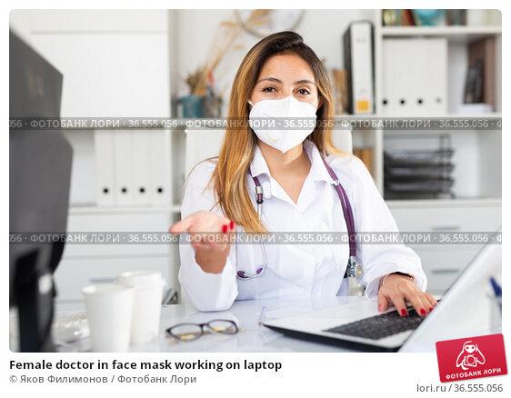 Female doctor in face mask working on laptop. Стоковое фото, фотограф Яков Филимонов / Фотобанк Лори