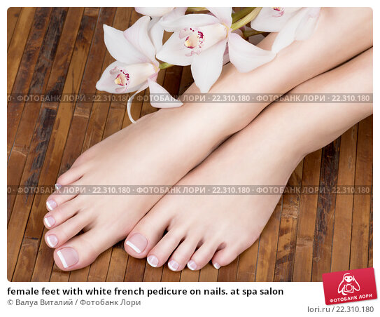 female feet with white french pedicure on nails. at spa salon, фото № 22310180, снято 31 марта 2015 г. (c) Валуа Виталий / Фотобанк Лори