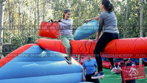 Female friends having funny wrestling by pillows on inflatable beam in outdoor amusement park. Стоковое видео, видеограф Яков Филимонов / Фотобанк Лори